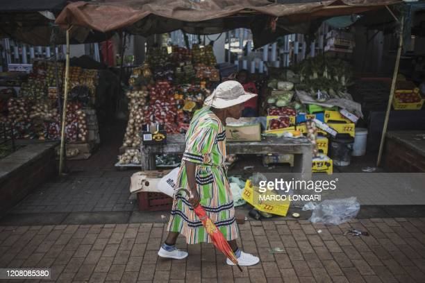 A woman walks by a food stall at an open air market in Kliptown Soweto on March 24 2020 South African President Cyril Ramaphosa on March 23 2020...