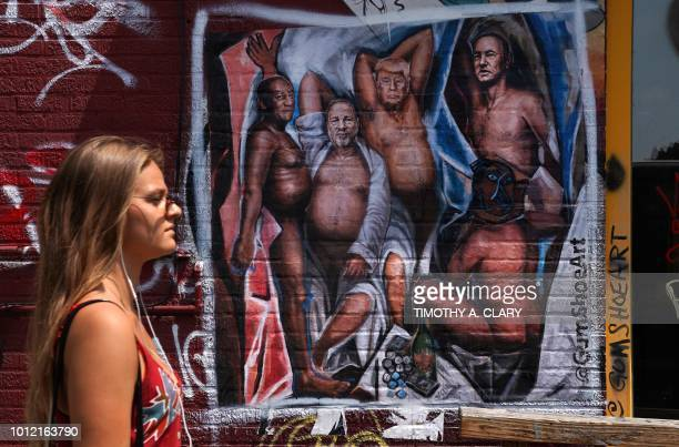 TOPSHOT A woman walks by a graffiti mural in the Williamsburg section of Brooklyn New York on August 6 2018 by New Yorkbased artist Angela China with...