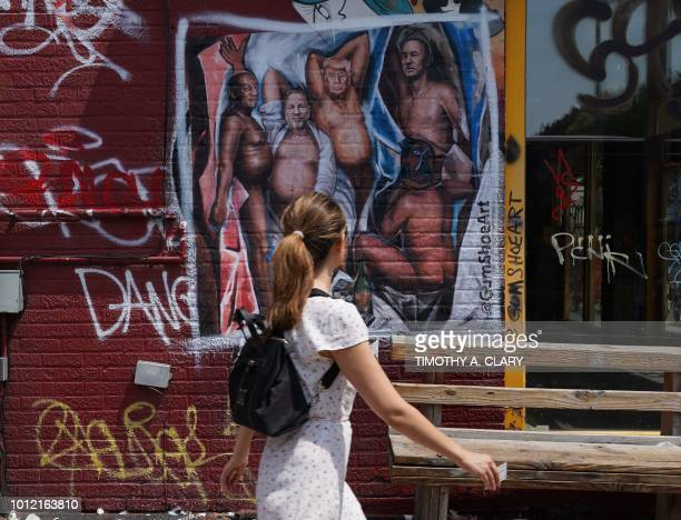 A woman walks by a graffiti mural in the Williamsburg section of Brooklyn New York on August 6 2018 by New Yorkbased artist Angela China with US...