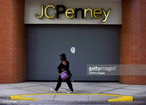 Woman walks by a JC Penney store that was temporarily closed on the day the company filed for bankruptcy protection and announced it would be closing...
