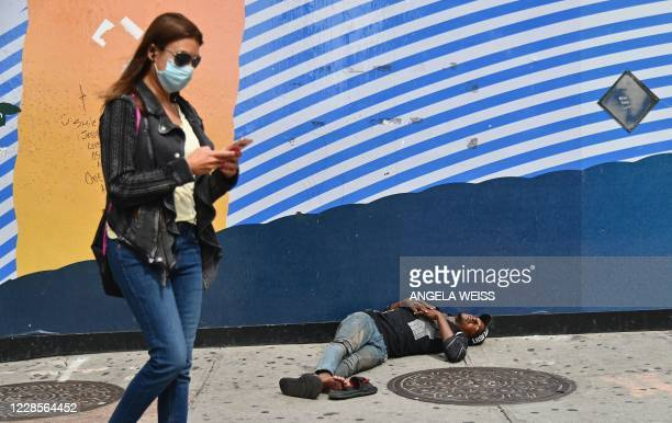 A woman walks by a man sleeping near Penn Station by Madison Square Gardens on September 17 2020 in New York City
