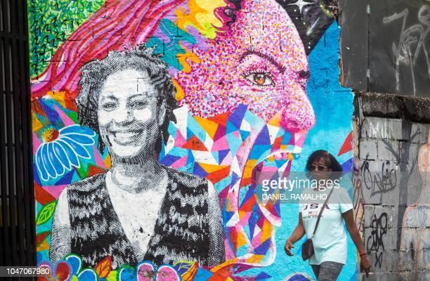 A woman walks by a mural depicting late activist Marielle Franco in the Estacio neighborhood of Rio de Janeiro Brazil during general elections in Rio...