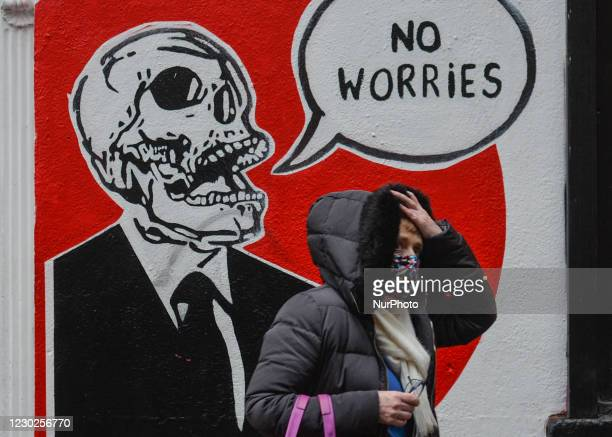 Woman walks by a mural in Dublin's Temple Bar. With the growing number of COVID cases and a dangerously contagious new COVID variant raging in the...