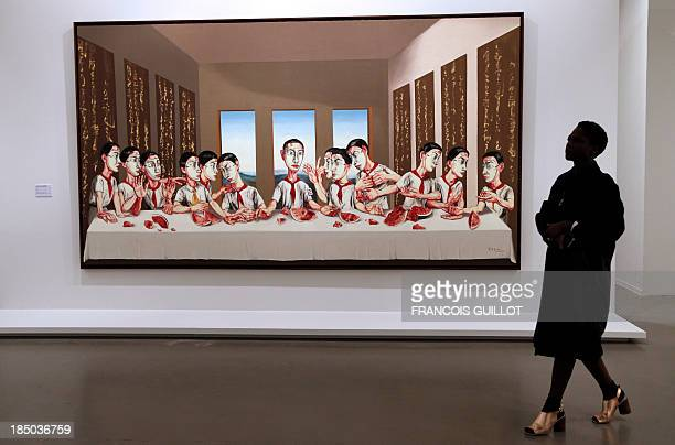 A woman walks by a painting by Chinese artist Zeng Fanzhi entitled 'The last supper' as she visits an exhibition dedicated to his work on October 17...