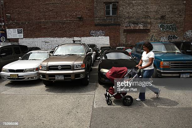 A woman walks by a parking lot July 13 2007 in auto congested New York City While real estate values fall in many parts of America in New York prices...