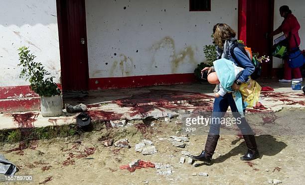 A woman walks by a pool of blood at the crime scene where ten people were shot dead by criminal gangs in San Isidro village near Santa Rosas de Osos...