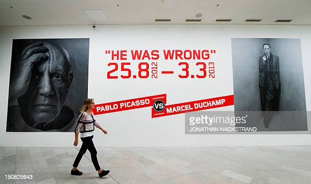 A woman walks by a poster of 'He was wrong' exhibition dedicated to Spanish artist Pablo Picasso and French artist Marcel Duchamp at the Moderna...