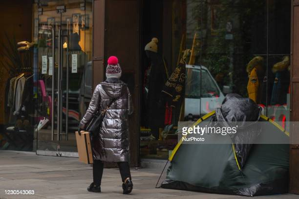 Woman walks by a rough sleeper's tent in Dublin city center during Level 5 Covid-19 lockdown. Ireland has the highest Covid-19 infection rate in the...