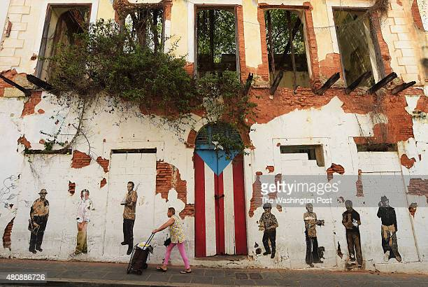 A woman walks by a rundown building on Saturday July 04 2015 in Old San Juan Puerto Rico The historic area brings in many tourists