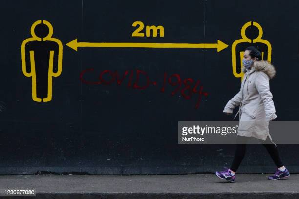 Woman walks by a sign 2metres in Dublin city centre during Level 5 Covid-19 lockdown. The Department of Health reported this evening 2,001 of new...
