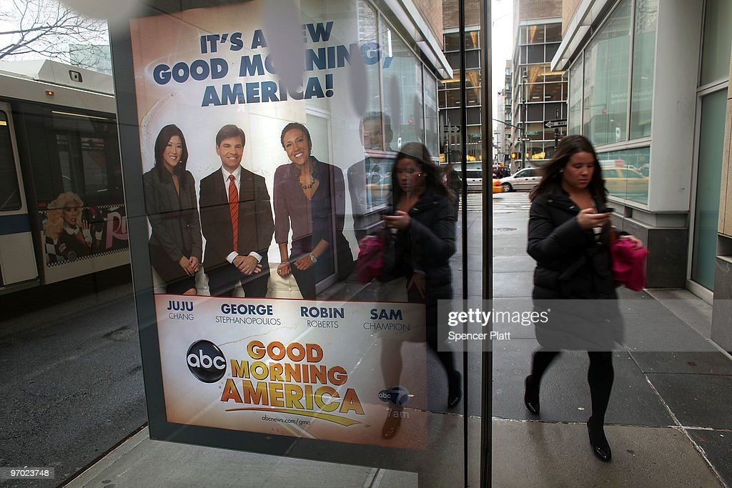 A woman walks by a sign advertising ABC news outside of ABC