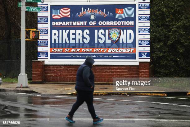 A woman walks by a sign at the entrance to Rikers Island on March 31 2017 in New York City New York Mayor Bill de Blasio has said that he agrees with...