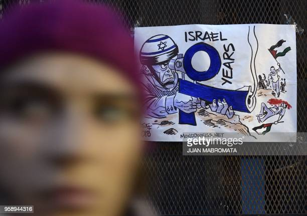 A woman walks by a sign during a protest against the killing of 60 Palestinians by Israeli fire in mass protests along the Gaza border as the United...