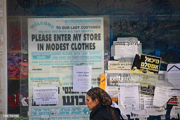 A woman walks by a sign in English requesting woman wear modest clothing in Beit Shemesh Israel on December 26 2011