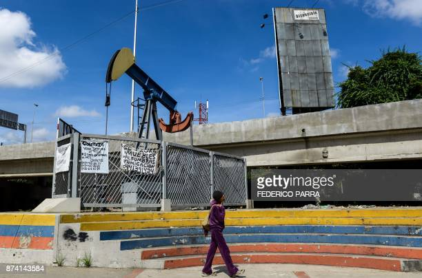 A woman walks by a small square with an oil pump in one of the access roads to the Central University of Venezuela in Caracas on November 14 2017...