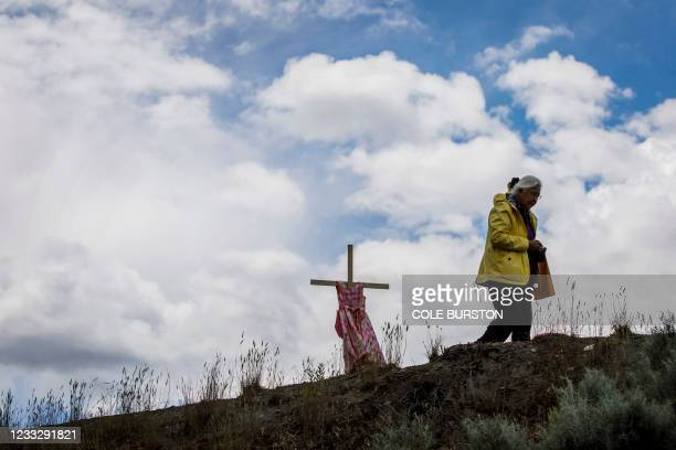 Woman walks by a staked child's dress on Highway 5, representing an ongoing genocide against First Nations people in Canada, near the former Kamloops...