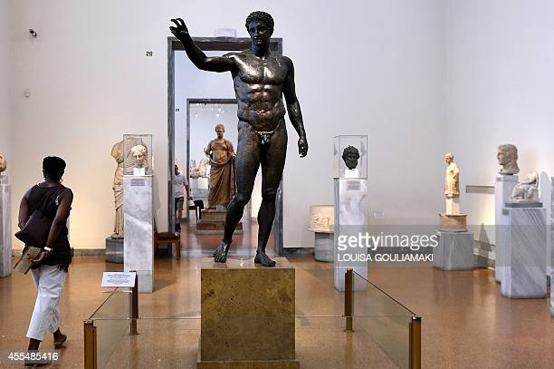 MAKRIS A woman walks by a statue of a youth displayed at the Archaeological Museum in Athens on September 14 2014 The statue was found in the wreck...