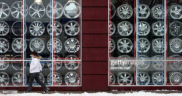 A woman walks by a store selling car accessories December 17 2008 in Detroit Michigan The Bush administration is vowing to support shortterm...