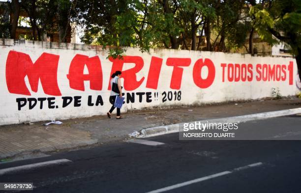 A woman walks by a wall displaying electoral propaganda of Paraguay's presidential candidate of the Colorado party Mario Abdo Benitez in Asuncion on...