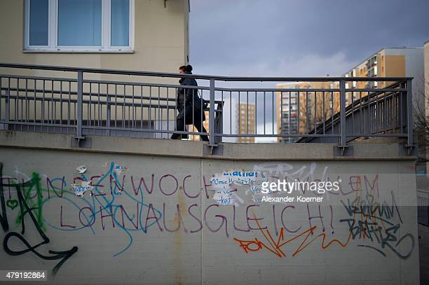 Woman walks by abandoned apartments, ready to be demolished, at dusk at an apartment complex on March 31, 2015 in Halle-Neustadt, Germany. The...