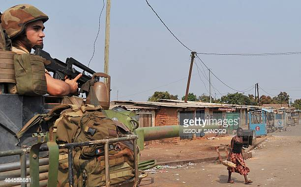 A woman walks by as a French soldier taking part in 'Operation Sangaris' stands guard at the PK 12 crossroad in Bangui following an overnight attack...