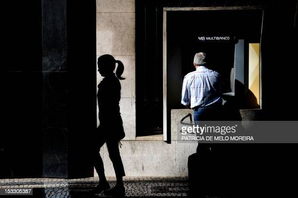 A woman walks by as a man uses an automatic teller machine in Lisbon on October 3 2012 The Portuguese government is set to announce a new round of...