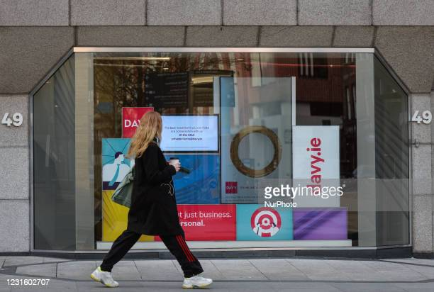 Woman walks by Davy headquarters in Dawson Street in Dublin. Davy is Ireland's largest stockbroker, wealth manager, asset manager and financial...
