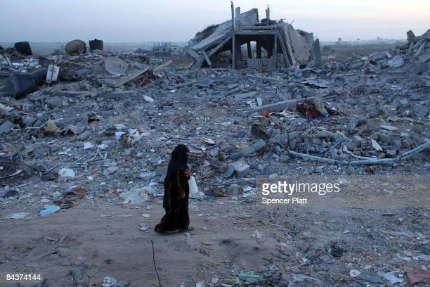 Woman walks by demolished homes January 20, 2009 in Jabalia, Gaza Strip. With a cease-fire holding between Hamas militants and the Israeli military...