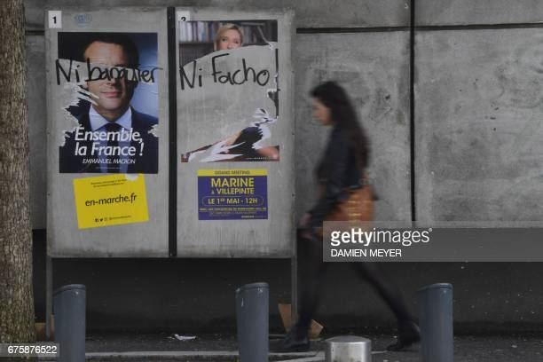 A woman walks by election campaign posters of French presidential election candidate for the En Marche movement Emmanuel Macron and French...