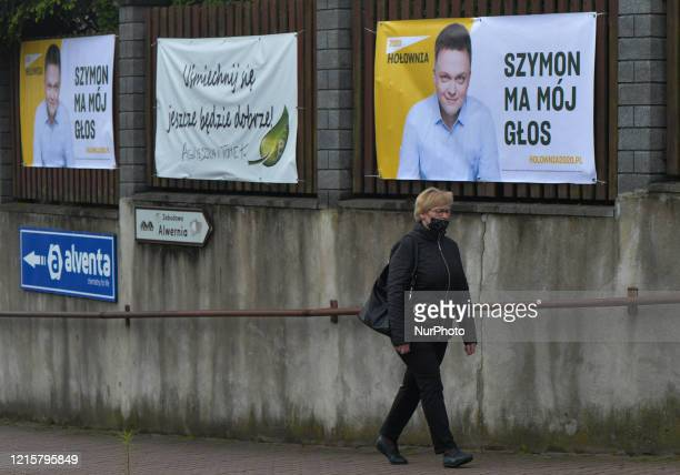 A woman walks by election posters of Szymon Holownia an independent candidate for the Presidential Election 2020 seen in Alwernia On Wednesday May 27...