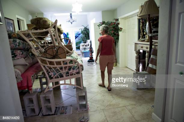 A woman walks by furniture sitting on cinder blocks in the foyer of her home as she and her husband prepare ahead of Hurricane Irma in Redington...