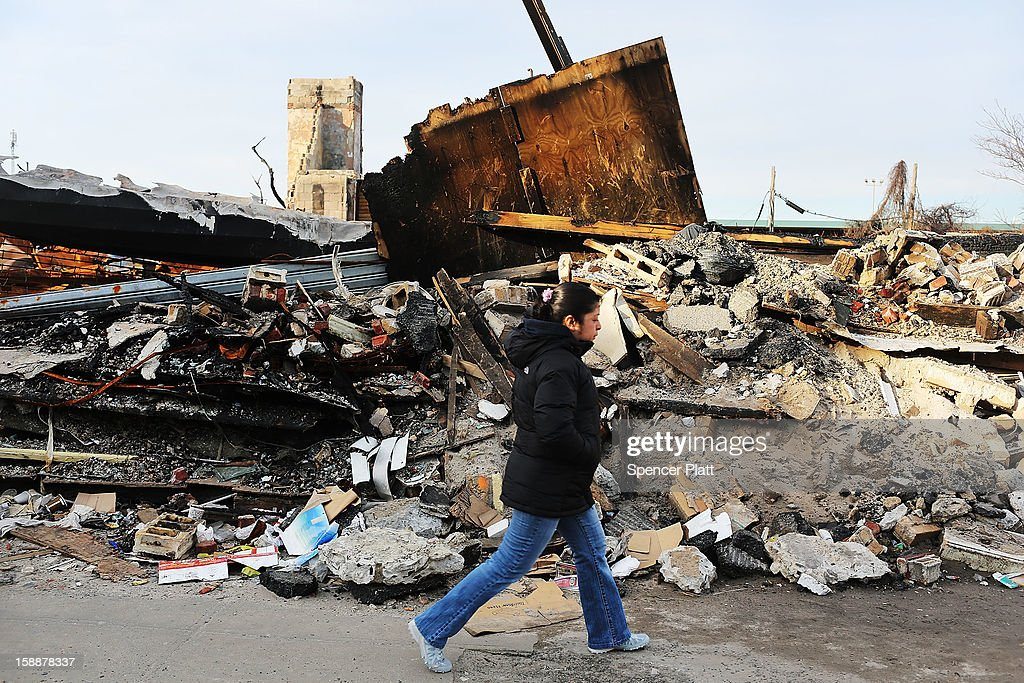 A woman walks by homes and businesses destroyed by Superstorm Sandy in the Rockaways on January 2, 2013 in the Queens borough of New York City. Criticism, including by President Barack Obama, has been directed at the Republican House's decision to adjourn without passing a Superstorm Sandy aid bill. According to early estimates, Superstorm Sandy inflicted at least $50 to $60 billion in damage across the Northeast, making it one of the most destructive storms ever.