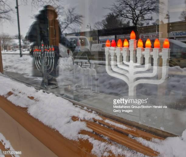 Woman walks by menorahs on display at Kolbo Fine Judaica on Harvard Ave. In Brookline . Saturday, December 20, 2008. Staff photo by Mike Adaskaveg.