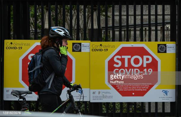 Woman walks by 'STOP COVID-19' signs seen on the Four Courts entrance gate, in Dublin, during Level 5 Covid-19 lockdown. On Thursday, 4 March in...