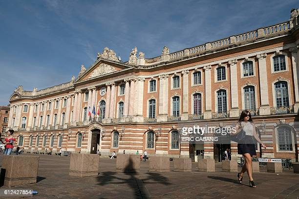 A woman walks by the city hall building at the place du Capitole in Toulouse on October 4 2016 / AFP / ERIC CABANIS
