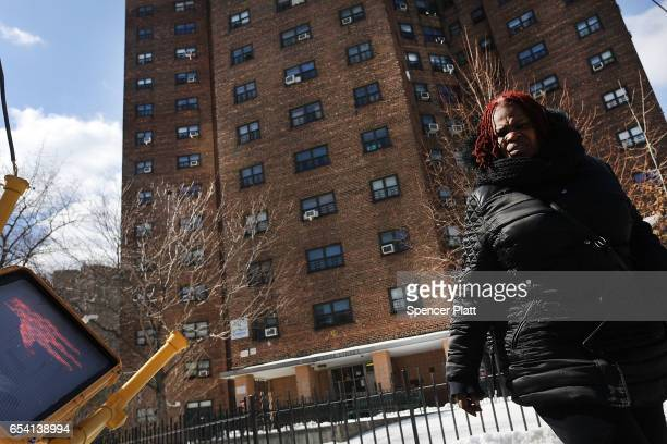 A woman walks by the Farragut Houses a public housing project in Brooklyn on March 16 2017 in New York CityThe budget blueprint President Donald...
