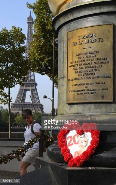 A woman walks by the Flame of Liberty statue plastered with iconic photos flowers and messages in tribute to Princess Diana on August 29 in Paris two...