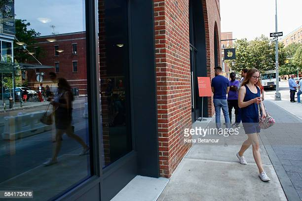 A woman walks by the new Brooklyn Apple Store during a media preview in the Williamsburg neighborhood of Brooklyn on July 28 2016 in New York City...