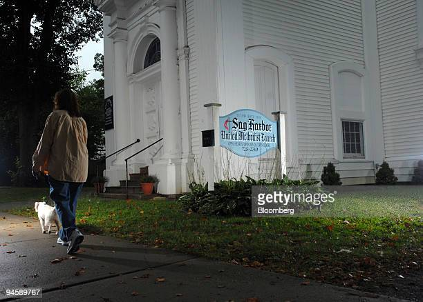 A woman walks by the Sag Harbor Methodist Church on Madison Street in Sag Harbor Long Island New York US on Tuesday Sept 11 2007 Dennis Suskind a...