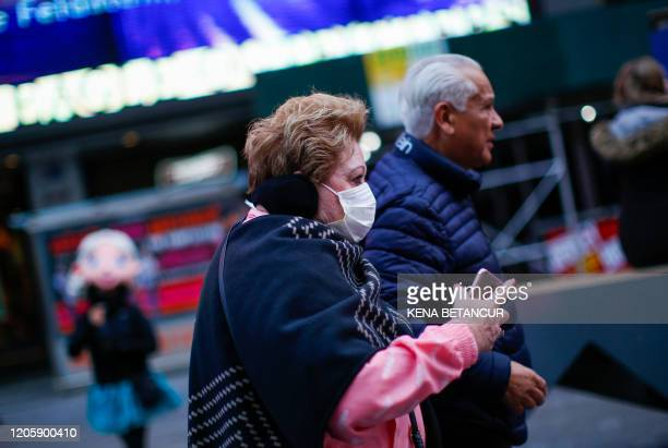 A woman walks by Times Square as she wears a face mask on March 8 2020 in New York City The governor of New York on March 7 2020 announced a state of...