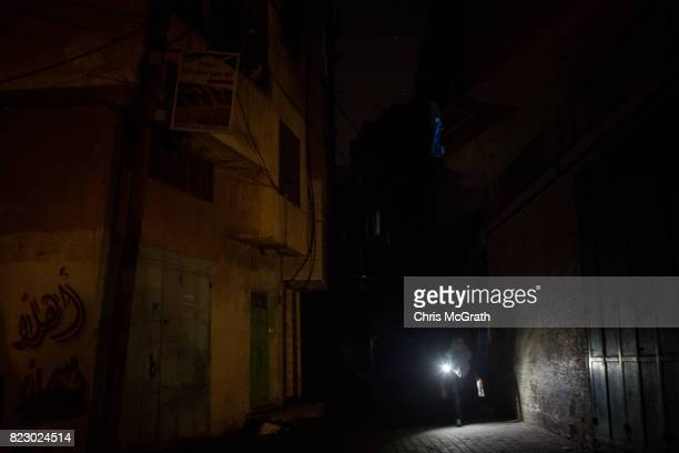 A woman walks by torch light in a downtown street on July 22 2017 in Gaza City Gaza For the past ten years Gaza residents have lived with constant...