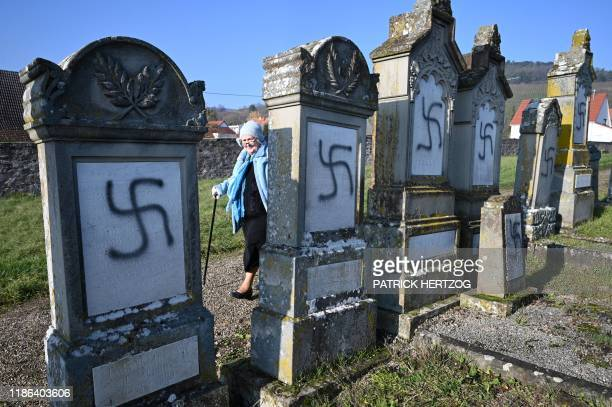 A woman walks by vandalised tombs on December 4 2019 at the jewish cemetery of Westhoffen near Strasbourg eastern France where 107 graves were found...