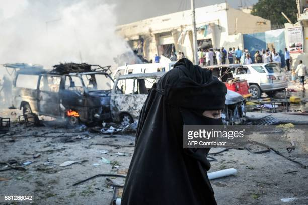A woman walks by wreckages of vehicles following the explosion of a truck bomb in the centre of Mogadishu on October 14 2017 A truck bomb exploded...
