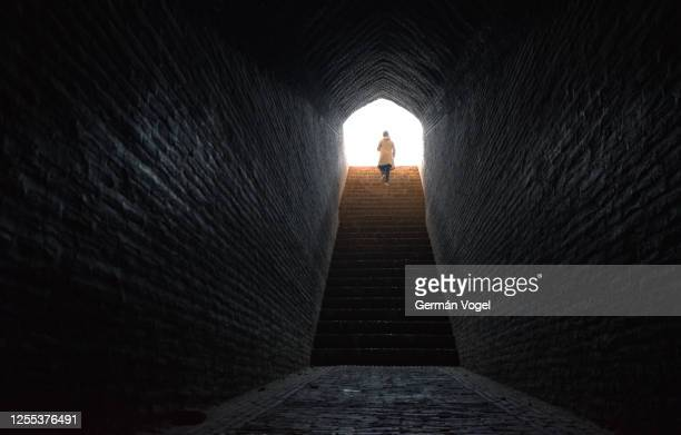 woman walks confidently up stairs coming out from dark tunnel into bright light, yazd, iran - appearance stock pictures, royalty-free photos & images