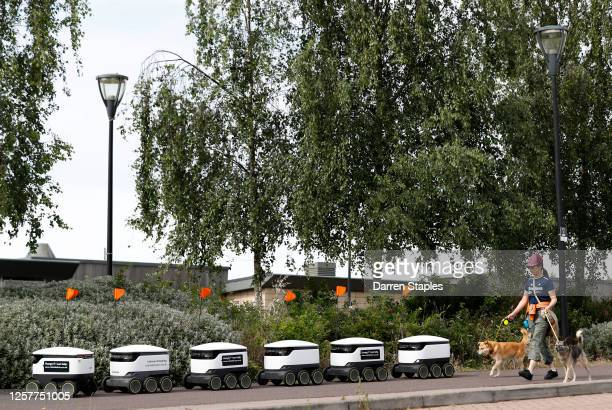 Woman walks dogs past Starship delivery robots waiting for orders during a visit from the Labour Leader Keir Starmer on July 23, 2020 in Milton...