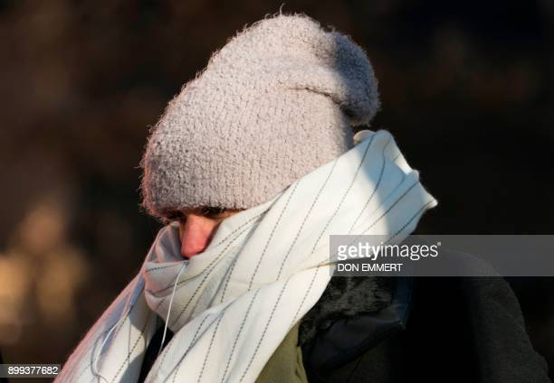 A woman walks down 50th Street bundled against the cold on December 28 2017 in New York as a bitter Arctic chill settled across much of the United...