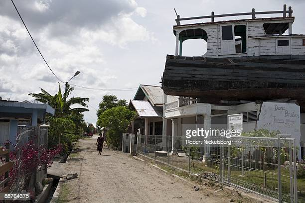 A woman walks down a Banda Aceh street where a fishing boat remains on the second story of a house following the December 26 2004 tsunami disaster in...