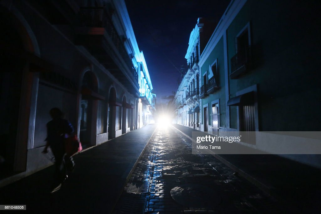 A woman walks down a darkened street past historic buildings in the touristic Old San Juan neighborhood, on October 13, 2017 in San Juan, Puerto Rico. Puerto Rico is suffering shortages of food and water in many areas and only 9 percent of grid electricity has been restored. The tropical island's tourism industry has collapsed. Puerto Rico experienced widespread damage including most of the electrical, gas and water grid as well as agriculture after Hurricane Maria, a category 4 hurricane, swept through.