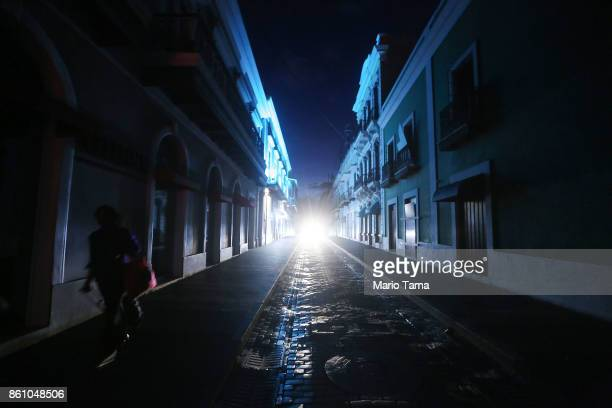 A woman walks down a darkened street past historic buildings in the touristic Old San Juan neighborhood on October 13 2017 in San Juan Puerto Rico...