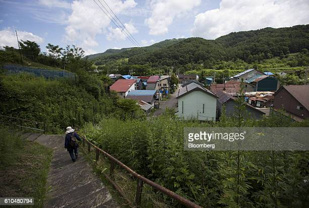 A woman walks down a flight of stairs as apartment blocks stand in the distance in Yubari Hokkaido Japan on Thursday July 21 2016 Yubari a former...